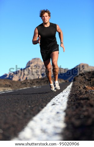 Man running in beautiful nature. Male runner jogging during work out training on mountain road. Young Caucasian fitness model with copy space.