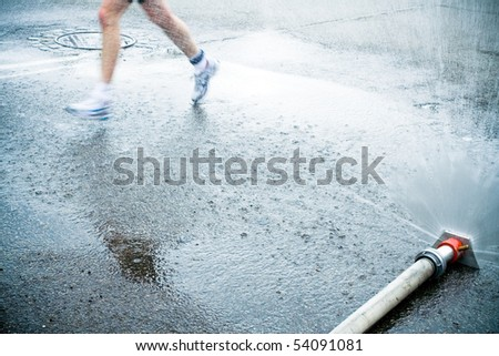 Man running in city marathon under shower, motion blur