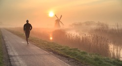 Man running in the foggy, Dutch countryside near a windmill during a tranquil sunrise. Shallow D.O.F.