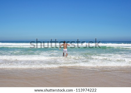 Man running in to indian ocean in south africa