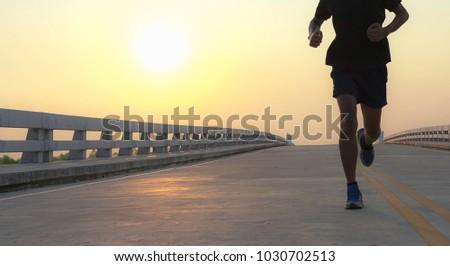 Man running jogging on bridge road. Health activities, Exercise by runner.  #1030702513