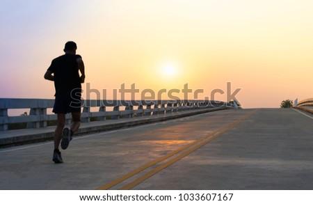 Man running jogging on bridge road. Health activities, Exercise by runner. #1033607167