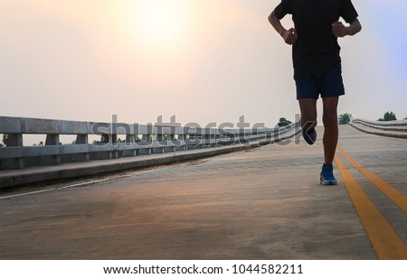 Man running jogging on bridge road. Health activities, Exercise by runner. #1044582211
