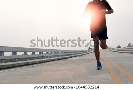 Man running jogging on bridge road. Health activities, Exercise by runner. #1044582214