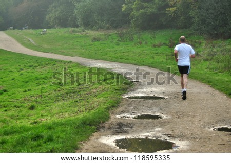 man running on a field road on a foggy autumn day