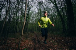 Man running outside in nature at rainy night with headlamp
