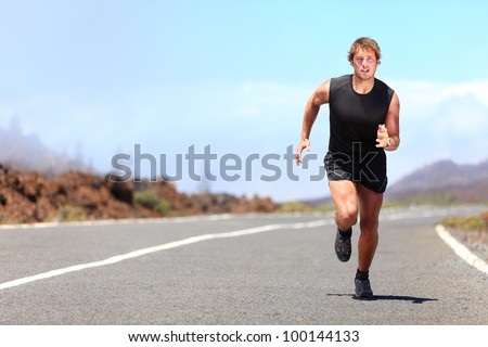Man running / sprinting on road in mountains. Fit male fitness runner during outdoor workout. Young caucasian man.