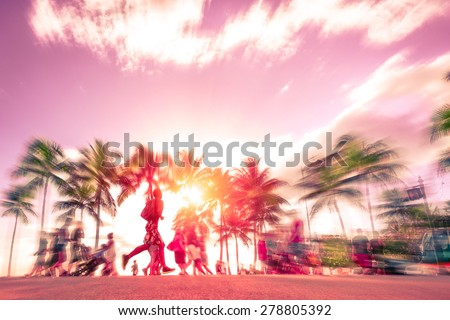 Man running through the crowd at sunset on Kalakawa Ave - Front walk promenade of Waikiki Beach in Honolulu Hawaii - Freedom and sport concept - Radial zoom defocusing with vintage marsala color tone
