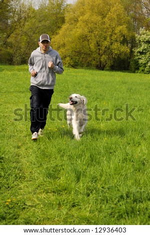 man running with his golden retriever dog in a meadow