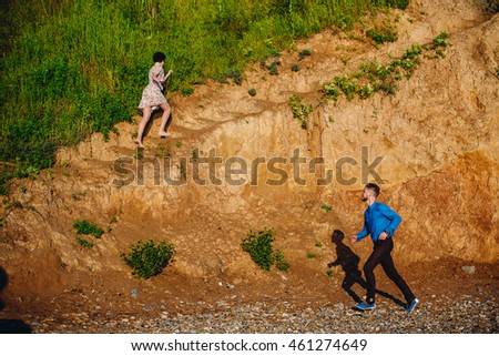 Man runs to the woman while she climbs the hill #461274649