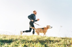 Man runs with his beagle dog. Morning Canicross exercise concept image