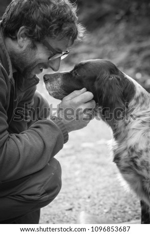 man's affection for his english setter dog in black and white #1096853687