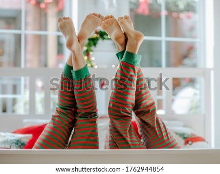 Man's and woman's barefooted legs up in red and green stripped Christmas pyjamas in white room. Copy space. Photo stock ©