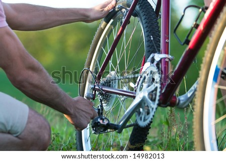 Man's arms fixing a bike in a grassy field. Horizontally framed photograph