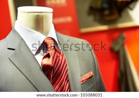 man's business suit shirt and necktie on mannequin in shop window