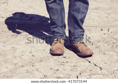 Man's dirty shoes and a very dry terrain in Finland. In the background out of focus shadow. Image includes a vintage effect. #417073144