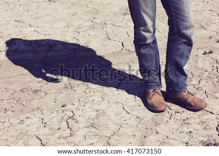Man's dirty shoes and a very dry terrain in Finland. In the background out of focus shadow. Image includes a vintage effect. #417073150
