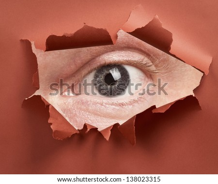 Man\'s eye spying through hole in paper