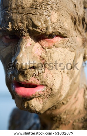 Man\'s face is very dirty in the mud. Dirt is not curative