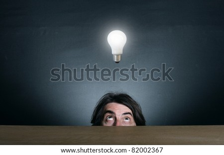 Man's face looking up at the burning light bulb. - stock photo
