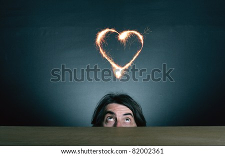 Man's face looking up at the sparkling heart pierced by an arrow.