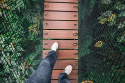 Man's feet and legs on wooden bridge over top of tree for sight seeing. Bridge covered by black net as wall.