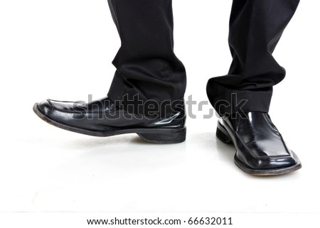 Man's feet in black trousers and black shoes - stock photo
