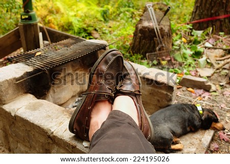 Man\'s feet in leather loafers resting on firepit with little dog napping in the background