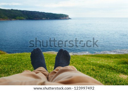 Man's feet relaxing on the grass facing the sea - stock photo