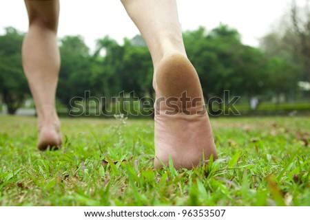 man's feet  running on the grass