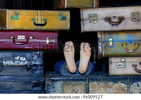 Man's feet sticking out of a pile of suitcases.