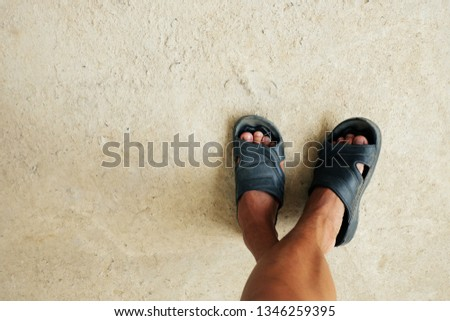 Man's feet wear sandals on the cement floor. #1346259395