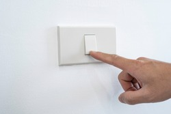 Man's fingers were turning off or turning the light switches on the white wall. Every time when not used for energy saving, electric energy saving concept.