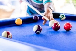 Man's hand and arm playing snooker in bar. Snooker ball on snooker table. Background. Copy space.