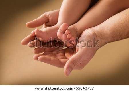 man's hand and children's foot isolated on a yellow background