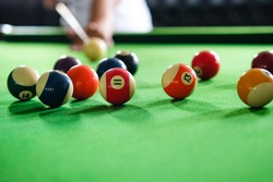 Man's hand and Cue arm playing snooker game or preparing aiming to shoot pool balls on a green billiard table. Colorful snooker balls on green frieze