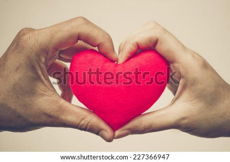 man's hand and woman's hand holding a red heart #227366947