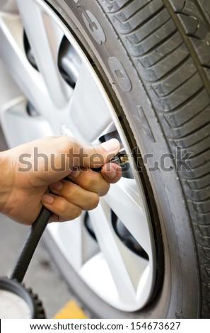 Man\'s hand checking tyre pressure.