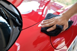Man's hand cleaning car and drying vehicle with microfiber cloth. Hand wipe down paint surface of shiny red sport sedan after polishing and ceramic coating. Car detailing and car wash concept.