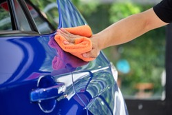 Man's hand cleaning car & drying vehicle with microfiber cloth. Hand wipe down paint surface of shiny blue sedan after polishing and ceramic coating. Car detailing, maintenance, and car wash concept.