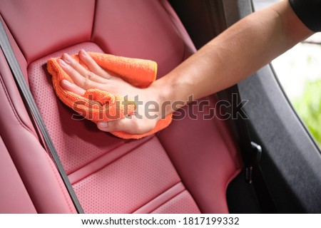 Man's hand cleaning red interior in luxury car with microfiber cloth. Hand wipe down leather seat of sports car.  Interior car detail and leather seat repair & cleaning background. Car wash concept. Foto stock ©