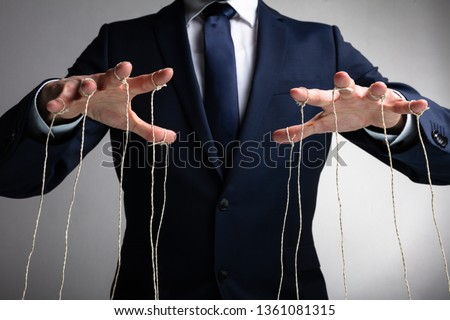 Man's Hand Controls The Puppet With The Fingers Attached To Threads Against Gray Background #1361081315