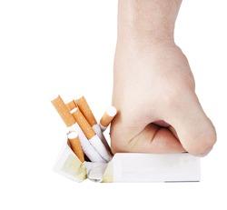 Man's hand crushing cigarettes on white background