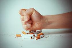 Man's hand crushing cigarettes. quit Smoking.