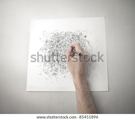 Man's hand drawing on a paper sheet