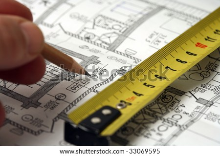 Man's hand draws a pencil business plan draft, with ruler