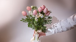 Man's hand giving bouquet of flowers. Hand of the man holding a beautiful bouquet of tulips flowers on pink background. Concept of Wedding, Valentine day, birthday. Beautiful  Flowers to gift