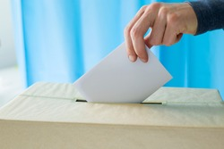 Man's hand holding a ballot paper for voting at a polling station during elections or referendum.