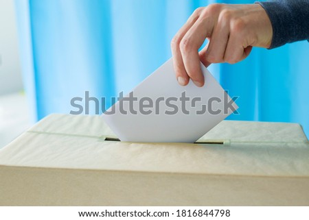Man's hand holding a ballot paper for voting at a polling station during elections or referendum. Сток-фото ©