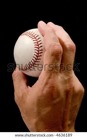 Man's hand holding a baseball in a pitching grip against black background